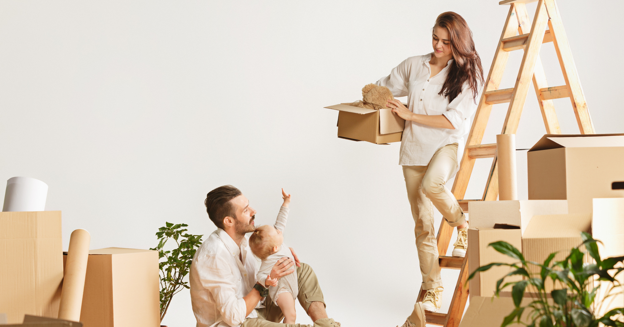 Two people unpacking in an new home. Man on the ground, woman on a ladder.