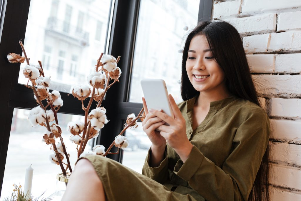 Image of a smiling asian young woman sitting at the cafe near window while chatting by her mobile phone. Looking aside.