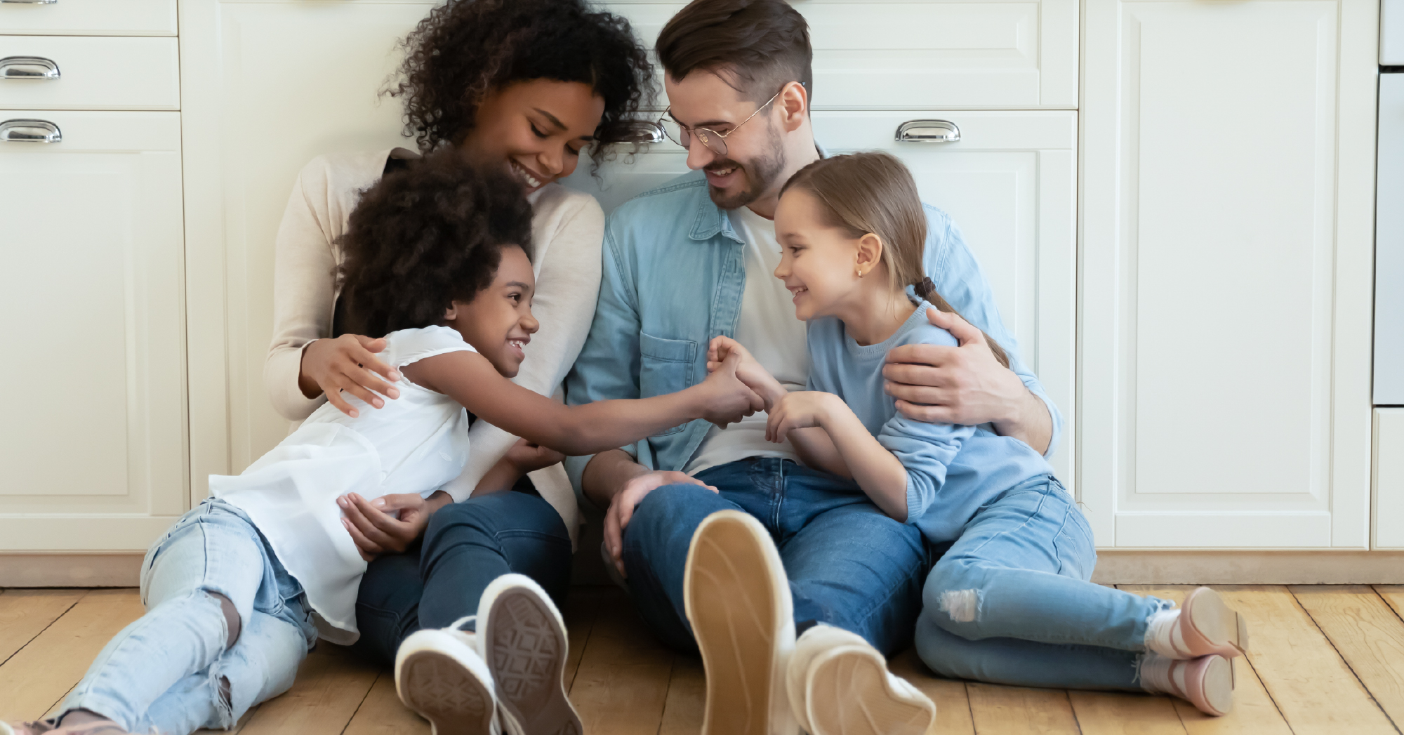 family sitting on a floor hugging and playing